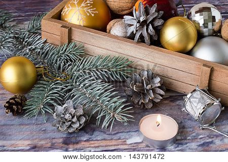 Wooden box with Christmas decorations, candle and spruce branch on old wooden table.