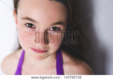 A close-up of a 10 year old girl close to a wall