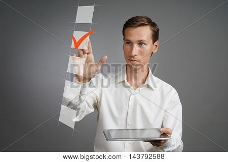 Young business man in white shirt with tablet computer checking on checklist box. Gray background.
