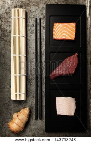 Assortment of raw fish and ingredients for making sushi on rustic background