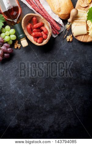 White wine, grape, bread, sausages and cheese on stone table. Top view with copy space