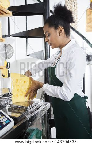 Saleswoman Packing Cheese At Counter In Grocery Store