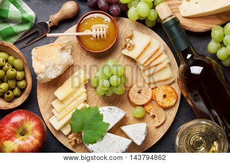 White wine, grape, bread, cheese plate and honey on stone table. Top view