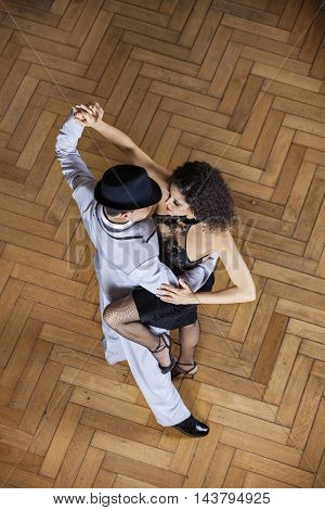 Passionate Man And Woman Performing Tango In Restaurant