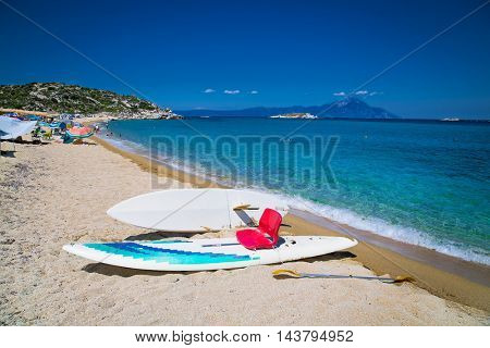 Surfboard  at beautiful Kriaritsi beach on the east coast of Sithonia on Halkidiki, Greece.