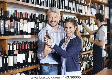 Couple Holding Wine Bottle While Salesman Working In Shop