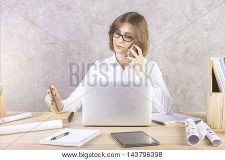 Businesswoman talking on phone while sitting at wooden office desktop with laptop tablet paperwork and other items