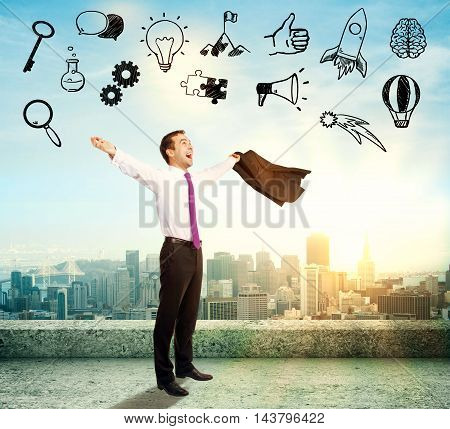 Businessman celebrating success on concrete rooftop with abstract business icons on city background with sunlight