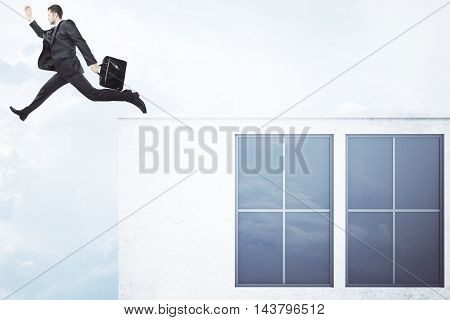 Businessman with briefcase jumping off roof of concrete building with windows and blank wall on sky background. Success concept. Mock up 3D Rendering