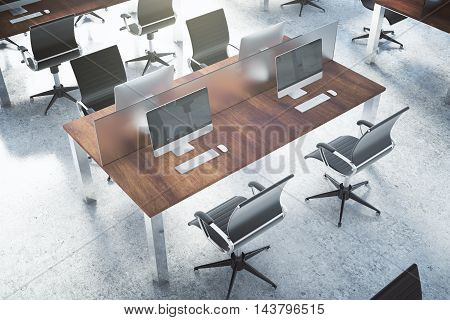 Top view of coworking office interior with concrete floor and multiple wooden desktops with blank computer screens. 3D Rendering