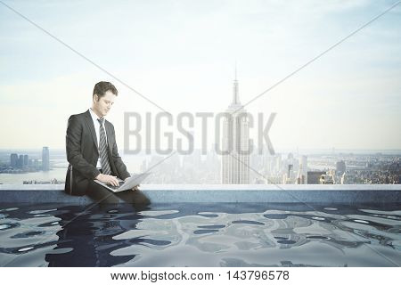 Young businessman using laptop on the edge of rooftop swimming pool with legs in the water. New York City background