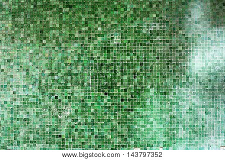 Green mosaic wall architectural background texture with small ceramic tiles in different shades of green in a repeat geometric square pattern in a full frame view
