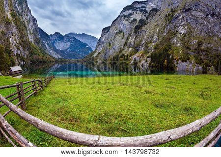 The concept of active tourism and ecotourism. Bavarian Alps. Magic blue lake Obersee and fenced path to it