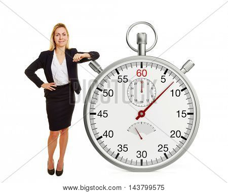 Smiling businesswoman leaning on huge oversized stopwatch