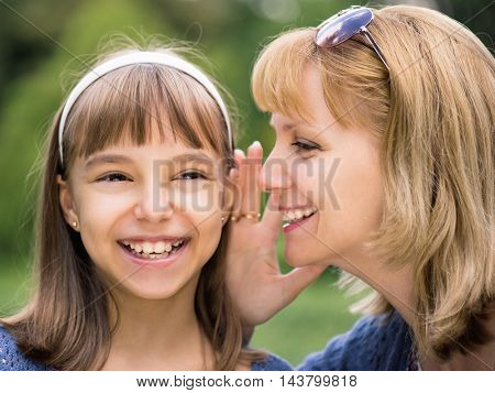 Smiling mother and daughter whispering gossip - relationships and happiness concept. Young woman telling her daughter a secret. Portrait of happy family - sharing secrets, outdoors at park.