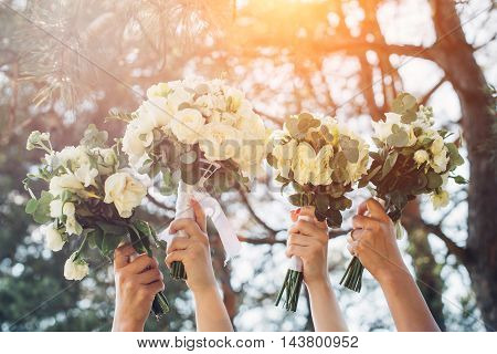 The bride and her friends held their wedding bouquets in hands