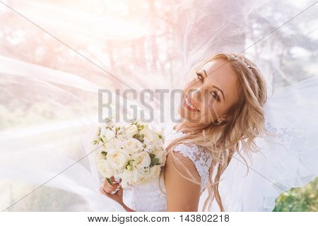 Happy bride on the day of his marriage poses for photographers