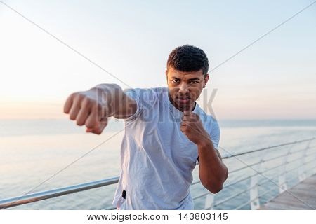 Focused african american young man athlete doing boxing training in the morning