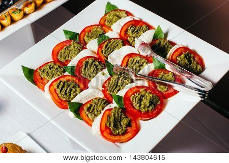 Traditional Italian caprese served on a plate, sliced tomatoes with pesto