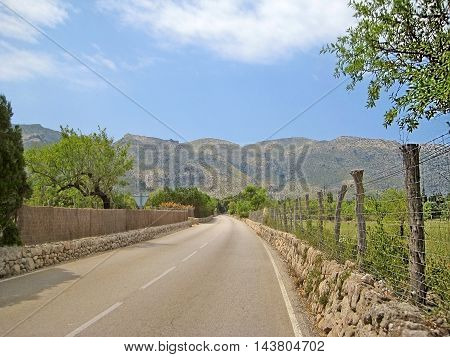 rural road in the mountains fence and stone wall