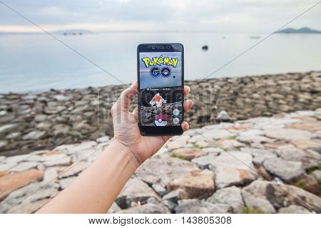Penang, Malaysia - August 13, 2016 : Man holding a smartphone with his left hand playing Pokemon Go game. Screen on the smartphone is a Pokemon character called