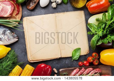 Vegetables, fish, meat and ingredients cooking. Tomatoes, eggplants, corn, beef, eggs. Top view with cookbook for copy space on stone table