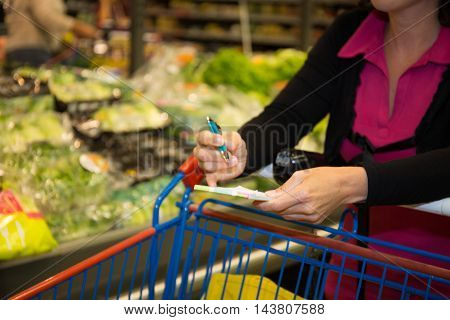 Woman Looking At Product List With Goods In Cart