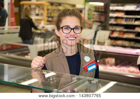 Young shop assistant with customer in the background
