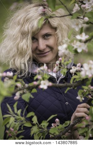 Portrait of beautiful woman with curly hair near of the blossom apple tree.
