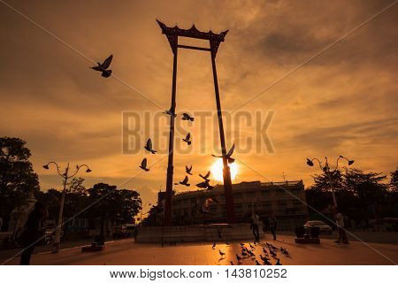 Silhouette of flying birds and giant swing at sunset time in Bangkok Thailand