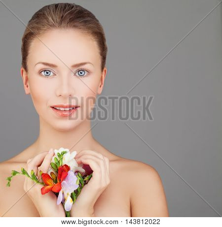 Spa Portrait of Perfect Woman with Beautiful Face Natural Makeup and Bright Colorful Flowers on Gray Background