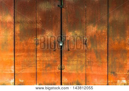Red iron door with a padlock to lock.