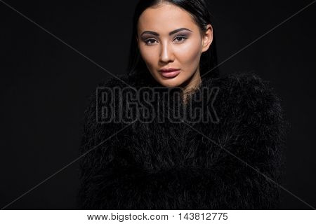 Portrait of gorgeous brunette model woman looking at camera in studio. Beautiful lady in black fur posing isolated on black background.