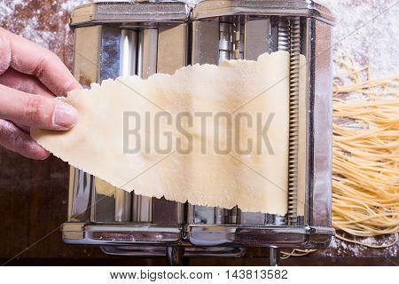 fresh homemade pasta and machine on kitchen table