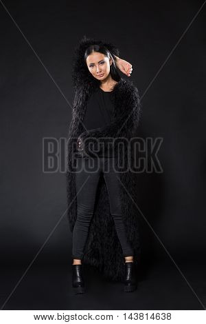 Picture of beautiful brunette model woman advertising or promoting fur coat while posing isolated on black background in studio.