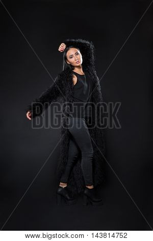 Picture of brunette model woman posing in fur coat isolaed on black background in studio. Beautiful lady posing for fashion or vogue magazine.