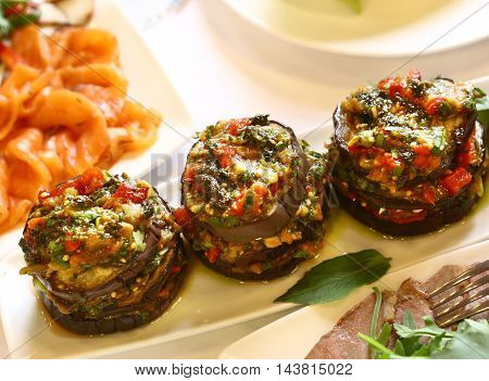 cooked eggplants with vegetables and mocarella on the plate close up photo
