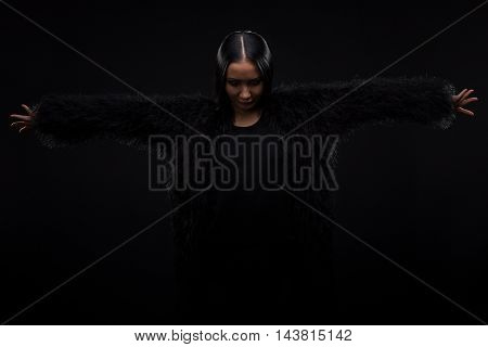 Picture of brunette model woman promoting or advertising expensive fur in studio. Beautiful lady posing isolated on black background.