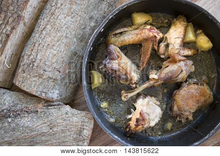 free-range chicken cooking in pan with potatoes