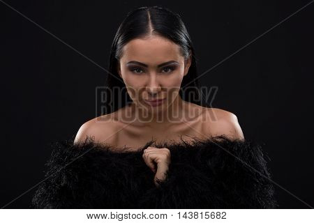 Closeup picture of pretty lady with perfect makeup isolated on black background. Brunette model woman posing in underwear or lingerie and fur coat on in studio.