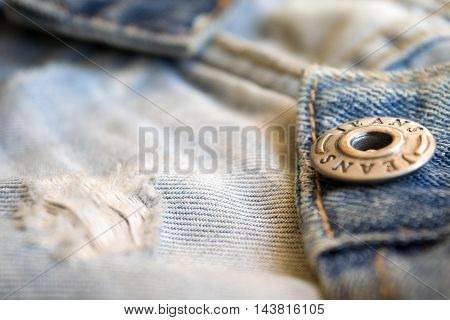 closeup of jeans clothing with metal buttons