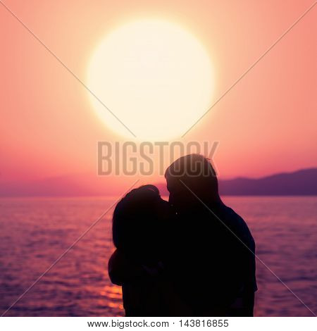 Young Couple Enjoying the Sunset on the Beach. Kiss. Silhouette of Man and Woman