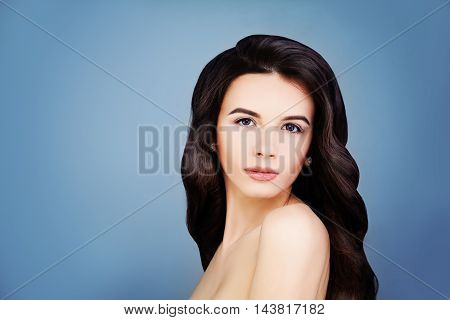 Haircare Concept. Healthy Brunette Girl with Long Brown Hair and Clear Skin. Portrait of Spa Woman