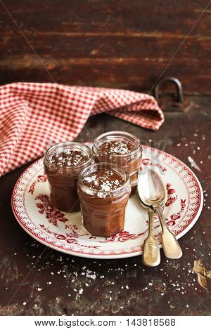 Dark chocolate mousse with freshly shredded coconut in jars on a wooden table, selective focus