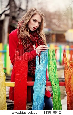 Romantic Woman wearing Red Autumn Coat and Scarf Outdoors