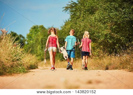 Siblings in nature. Two girls and one boy holding toys and going to play.