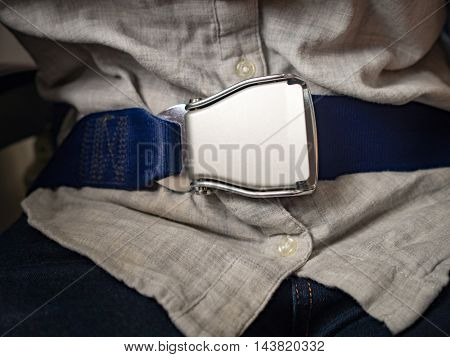 Passenger wearing seat belt in Airplane to save life while flying in sky. Safety and travel concept.