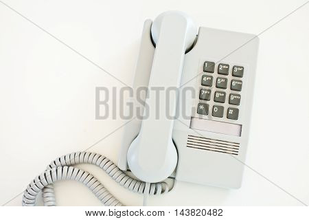 Push button telephone on white surface. Top down view.