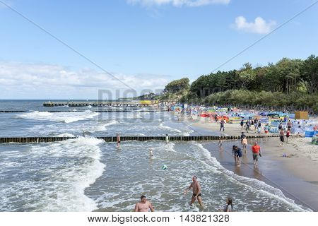 USTRONIE MORSKIE - AUGUST 15: Tourists enjoy the sunny weather and relaxing on the Baltic sea beach on 15 August 2016 in Ustronie Morskie, Poland.