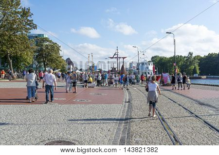 KOLOBRZEG - AUGUST 15: Tourists enjoy the sunny weather and walking on the harbor on 15 August 2016 in Kolobrzeg, Poland.